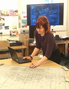 Hannah at work with the Cook, Welton & Gemmell ship plans