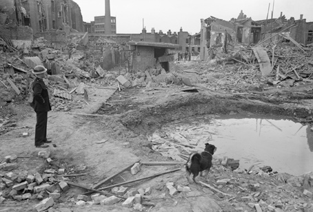 An Air Raid Precautions warden (ARP) and his dog survey devastation from a bombing raid in Poplar, east London.
