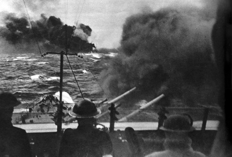 In April 1942 a Royal Navy cruiser fires at Italian naval vessels. A smoke screen covers the convoy's passage to Malta.