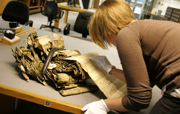 A researcher working with a delicate resource at The National Archives