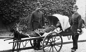 Photograph of two policemen with a man on a stretcher, 1884 (Catalogue reference: COPY 1/369)