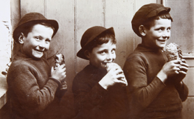 Photograph of three boys eating pasties, 1911 (Catalogue reference: COPY 1/555/212)