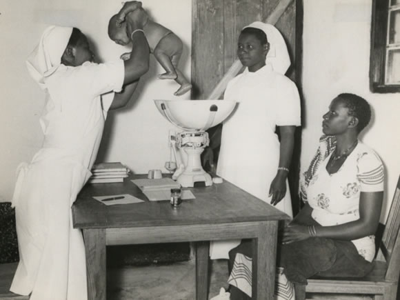 Village midwife, Rachel Yusuti (holding the baby), Mnyiramba and Ayah Brina Masasi, Msukuma, Weighing an infant and giving advice to the mother during an infant welfare clinic session at Kishapu Native Authority Dispensary and Clinic in Shinyanga District, Lake Province - Catalogue reference: CO 1069/157