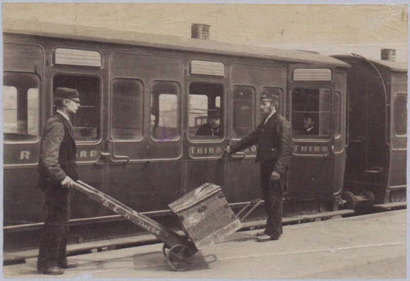Photograph of two railway porters, one wheeling a box on a truck, another shutting the door of a third class carriage, 1884 (COPY 1/369 f.255)