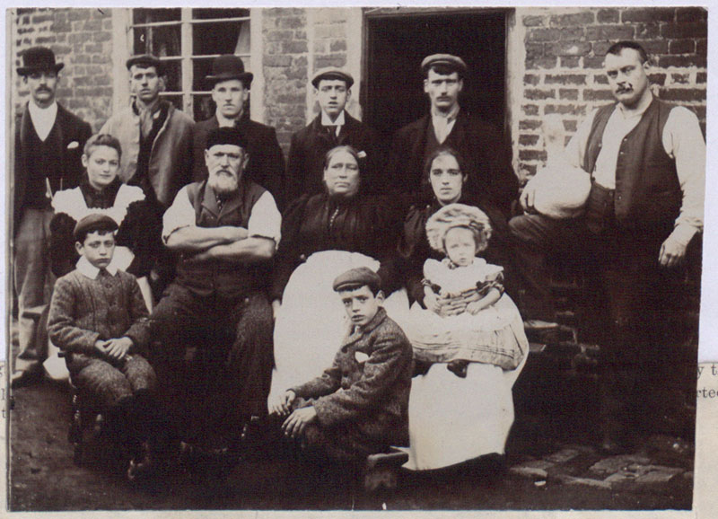 Photograph of a working class family group: Mr and Mrs Lowe and son (Mr Lowe is holding the goose) with Mr and Mrs Harvey and others, 1901 (COPY 1/450 f.3)
