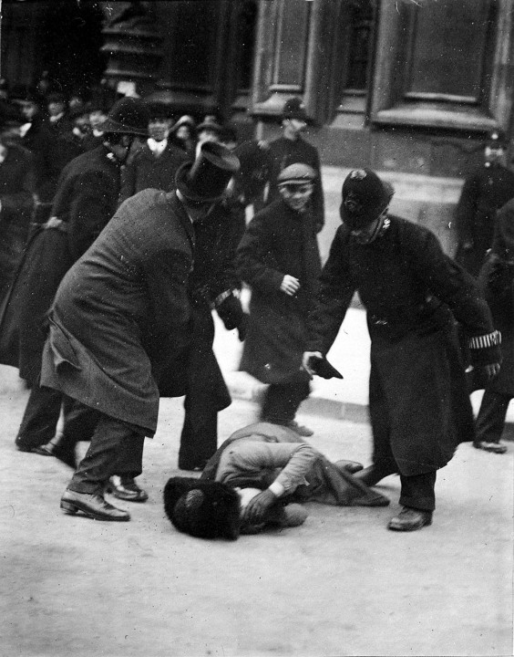 A women lies on the floor covering her face, at Black Friday demonstration in November 1910; she is surrounded by four men