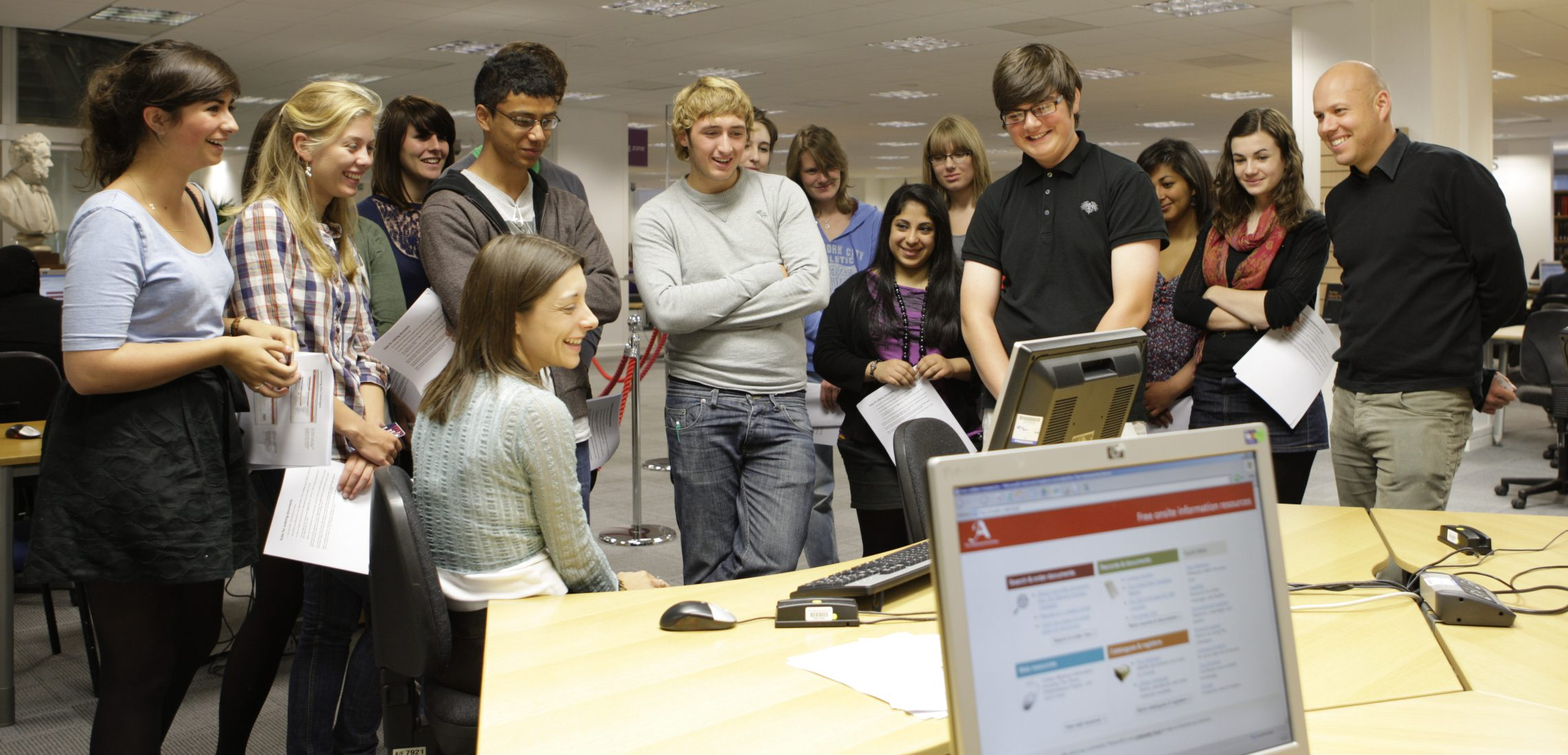 A group of students gather around a computer terminal within The National Archives