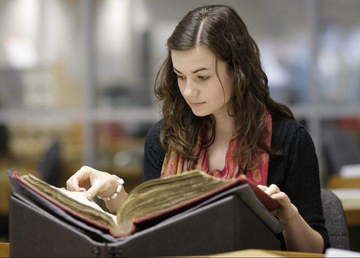 Young woman turns the pages of a document resting on a supporting aid