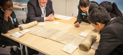 A group of students lean in to look at a medieval scroll