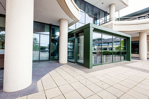 Outside view of the front entrance porch, outer sliding doors to inner revolving door, and accessible doors.