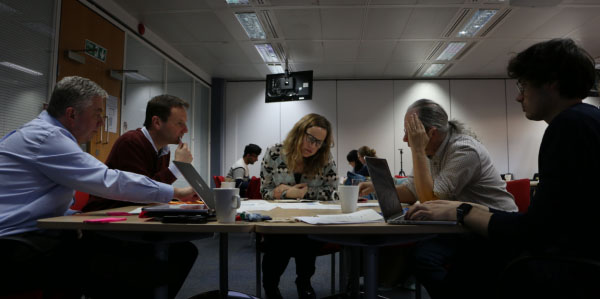 Five people sit round a table with laptops and papers on the table, looking down at some of the papers. There are three more people at another table in the background.