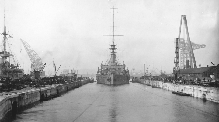 Portsmouth Dockyard, 1914. This is HMS Hindustan entering Dock No.14 (catalogue reference ADM 195/84). Cranes are visible on either side of the canal into which the ship is docking.