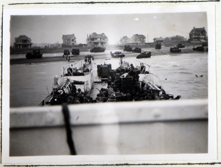 Operation Neptune landing craft during the D-Day Landings in June 1944 (catalogue reference ADM 199/1660). In the foreground are troops and landing craft readying to leave a boat approaching the shore; int he background are tanks and other vehicles on a beach in front of several detached houses.