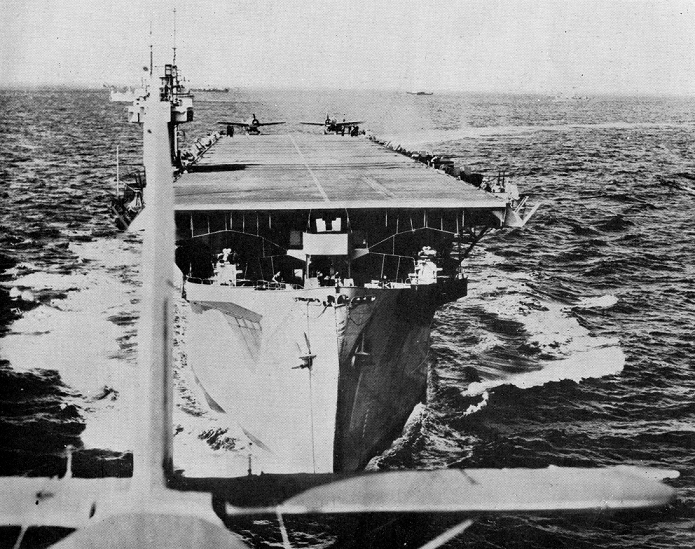 A shot of HMS Biter, a convoy escort carrier, at sea, taken from the back of an aeroplane which has apparently just taken off from the carrier, in 1944 (catalogue reference ADM 199/2061).