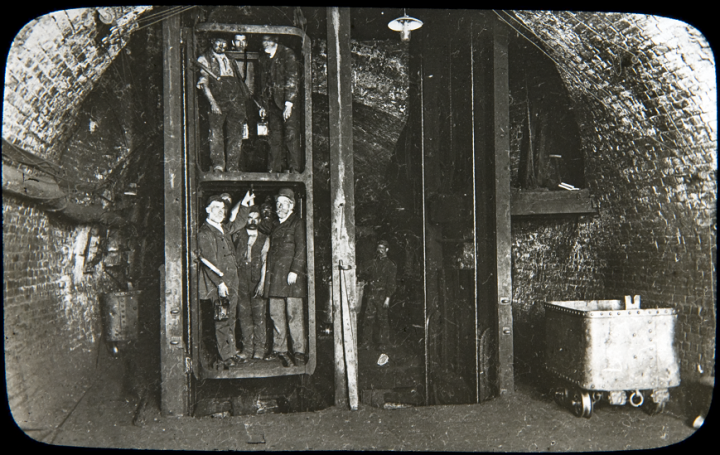 Miners squeezed into an underground lift in an underground chamber. This image is from a collection of photographs, inherited by the National Coal Board, taken by Reverend FW Cobb, Rector of Eastwood, Nottinghamshire between 1907 and 1914 (catalogue reference COAL 13/24).