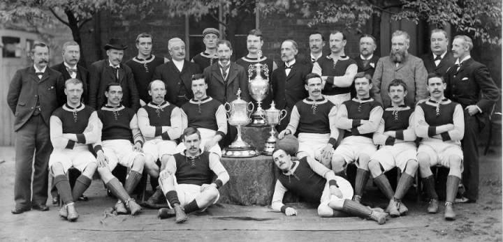 A cropped version of a photograph of Aston Villa Football Club, showing the whole team in club colours and ten older men in suits, gathered around three trophies. The photo was registered for copyright in 1896 (catalogue reference COPY 1/424/87).