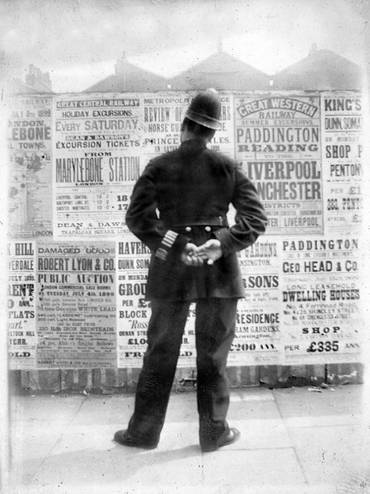A rear view of a policeman stood in front of a wall of bill posters with his hands behind his back, apparently reading the posters.