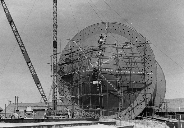 A giant metal cylinder covered in scaffolding supporting two workmen. This is the construction of the 'Conun' drum in 1943, used to lay pipe under the English Channel for the Pipe Line Under The Ocean (PLUTO) project (catalogue reference POWE 45/61).