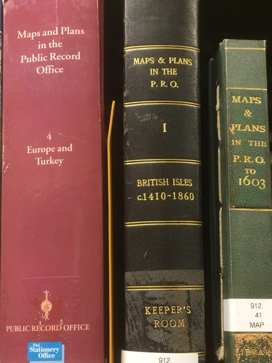 The spines of three hardback books - some of the published catalogues of maps and plans held at The National Archives (previously the Public Record Office).