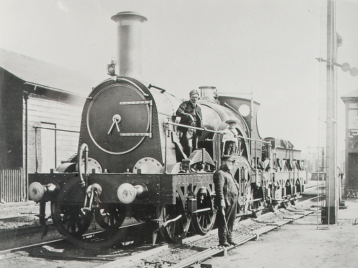 A broad gauge 'Lightning' locomotive of the Great Western Railway, stationary in a yard, 17 July 1889 (catalogue reference RAIL 1014/19). A man and a child are shown stood on the side of the locomotive and another man is stood on the ground in front.