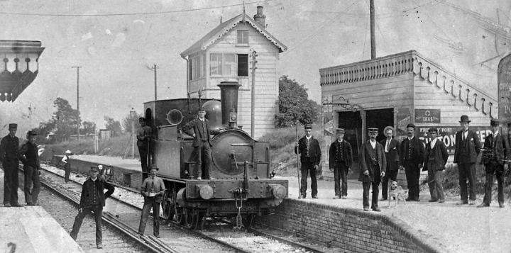 A locomotive engine stationary at Ludgershall train station, on the Midland and South Western Junction Railway, in 1901 (catalogue reference RAIL 1014/36/16). Fourteen men pose for the camera, stood side by side across the platform, on the tracks and on the locomotive itself.