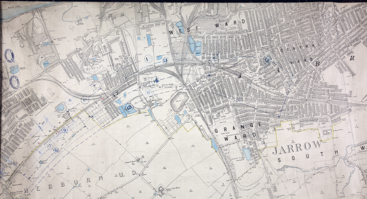 A grey Ordnance Survey map showing lots of detail, used for railway planning, showing Hebburn Station near Tyne Dock in north-east England (catalogue reference RAIL 1037/183). Individual buildings are distinguishable and there are blue blobs representing mineral deposits.