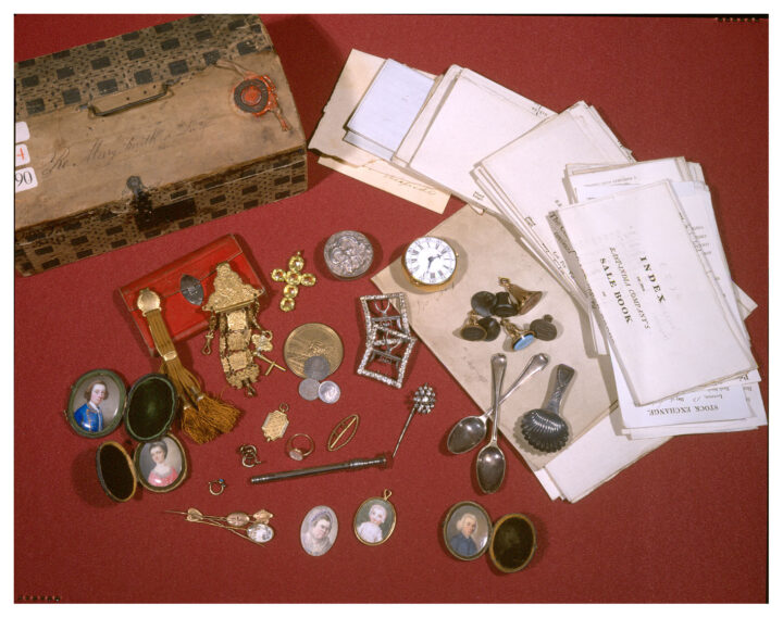 A collection of small objects including miniature portraits and spoons next to a pile of letters and a small wooden box.