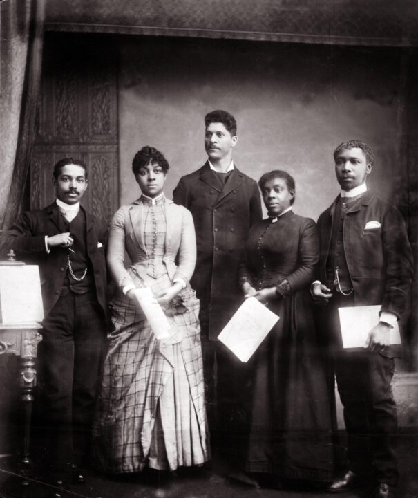 Monochrome photograph of a group of Black men and women. They are dressed in Victorian clothing and posing as a group for the camera.