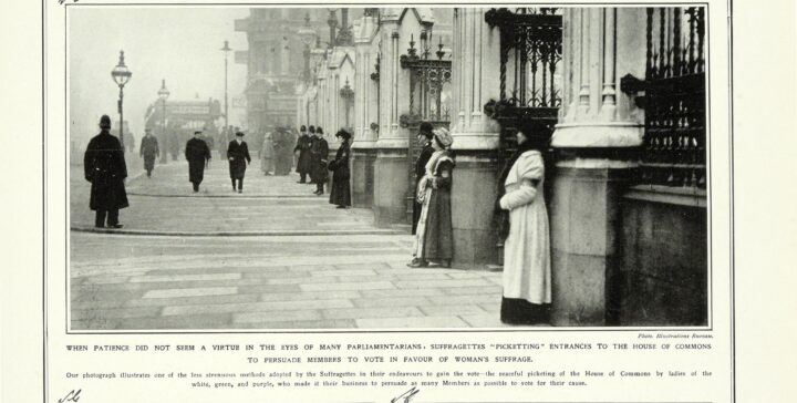 Monochrome photograph of women standing still in front of the pillars of the House of Commons.
