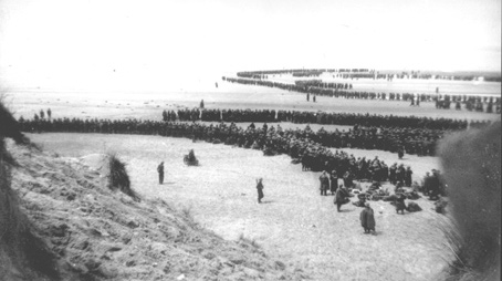 May 1940, British troops await evacuation on the beach at Dunkirk.