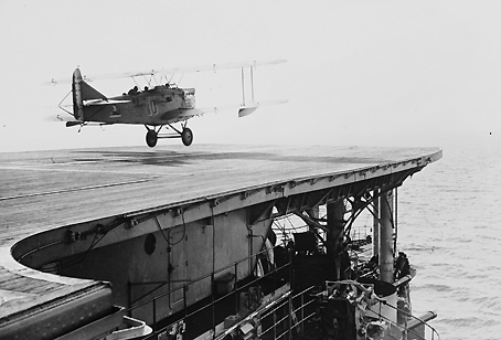 A biplane takes off from an aircraft carrier in the 1930s.