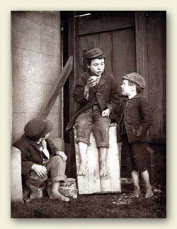 Three school boys wearing caps, rough woollen jackets, vests and knee-pants or rolled trousers but they have no shoes. From the beginning of compulsory education, there were always boys prepared to 'mooch off' and take an unauthorised holiday. Ref:COPY 1/436, Part 2