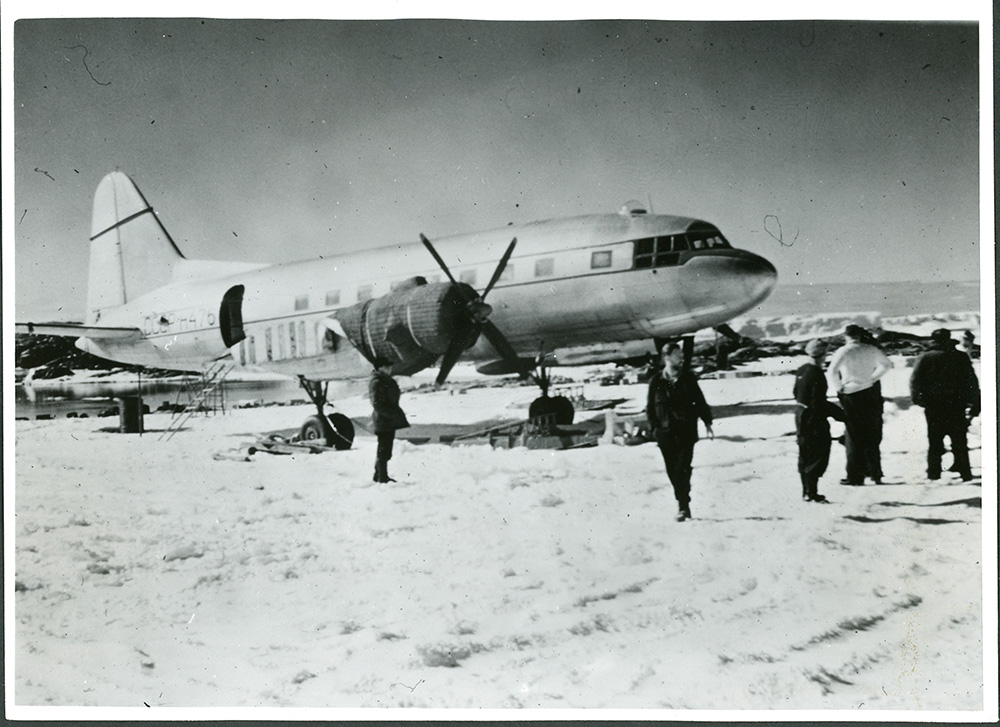 Black and white photograph of a small plane on ice-covered ground