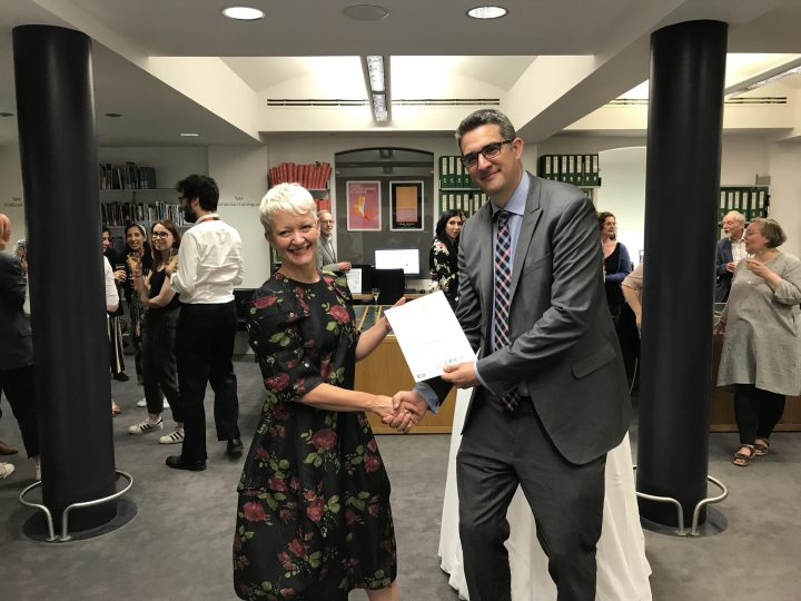 A photograph. Neil Curtis (Finance and Commercial Director) presents Maria Balshaw (Director of Tate) with Tate's Archive Accreditation Certificate