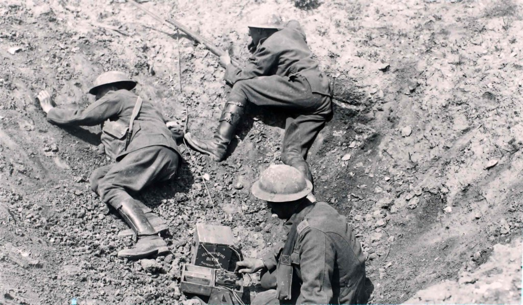 Soldiers in trench hole using a morse code machine (BT Archives cat ref: TCB 417 E36705)