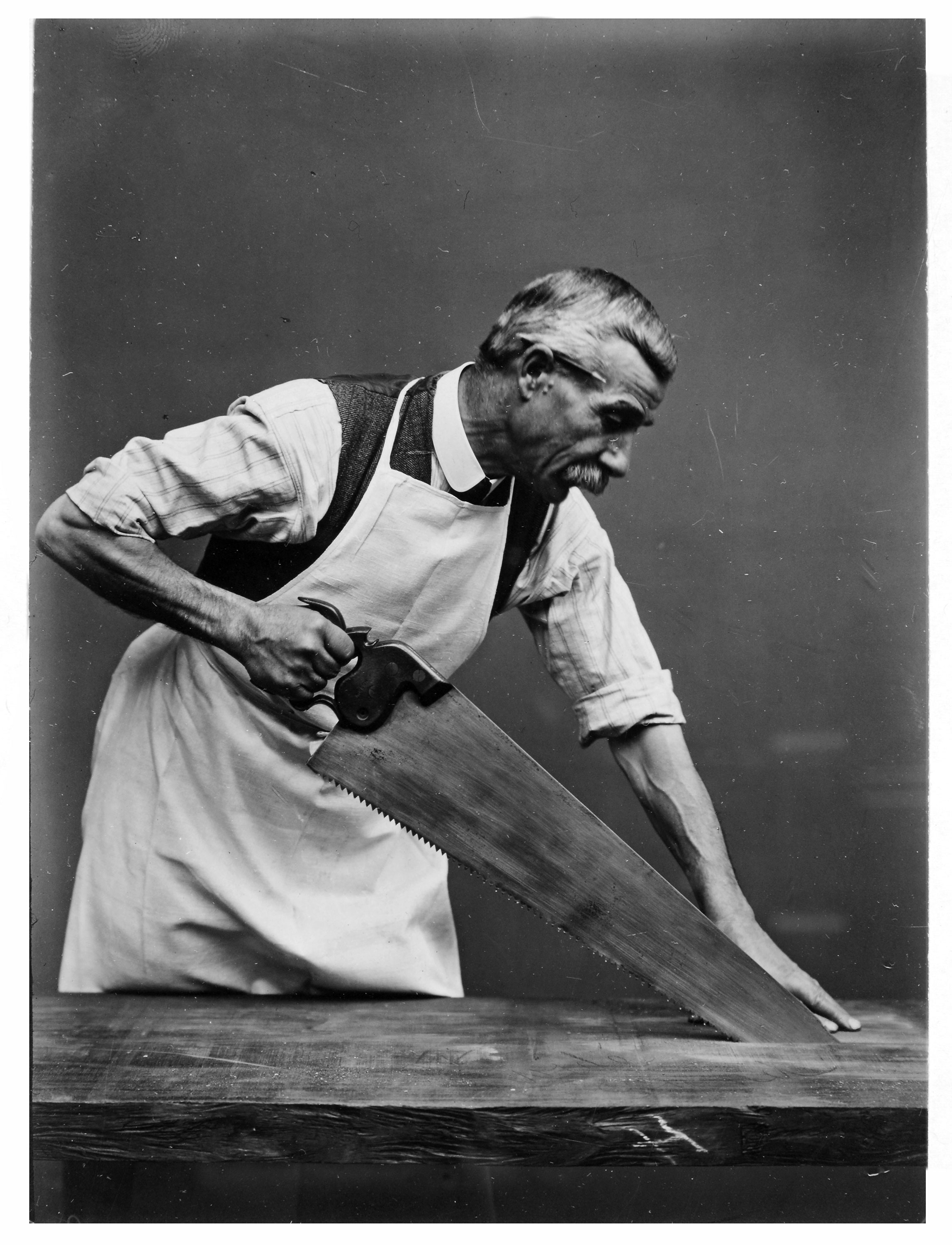 A photograph of a man using a handsaw to cut a piece of wood