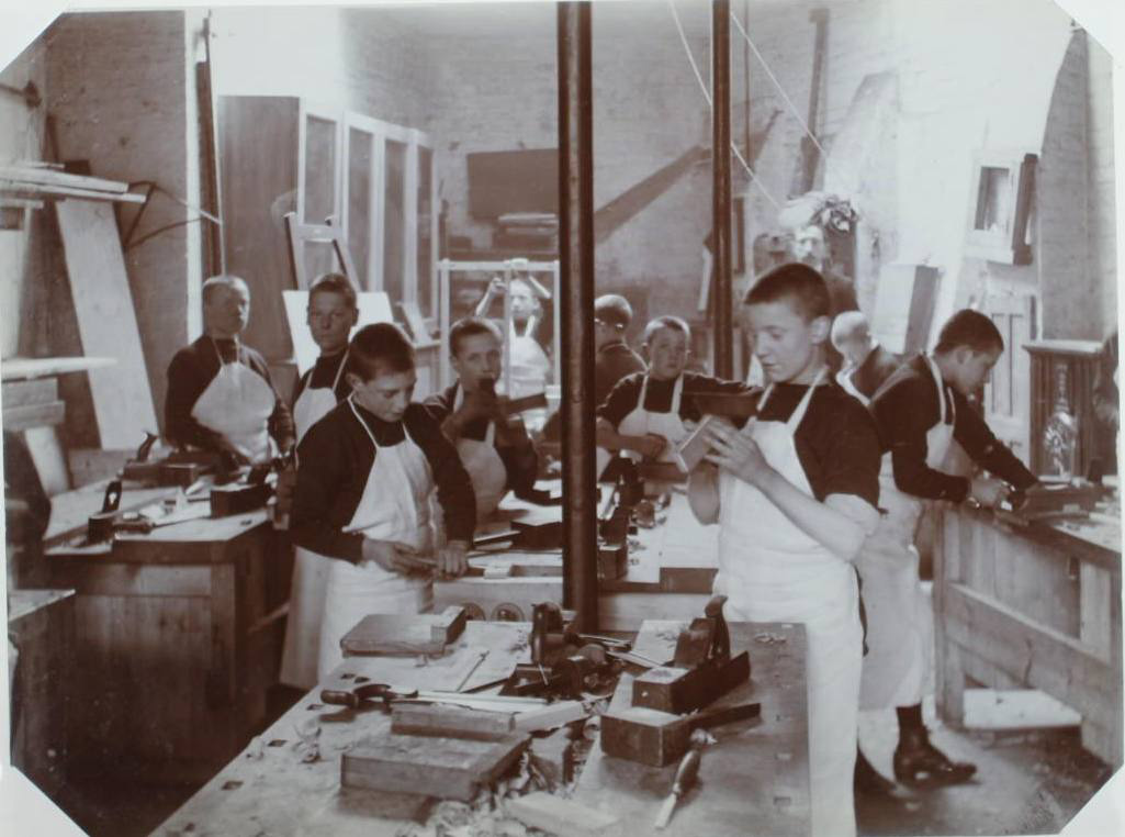 Image of a black and white photograph of children in a school workshop